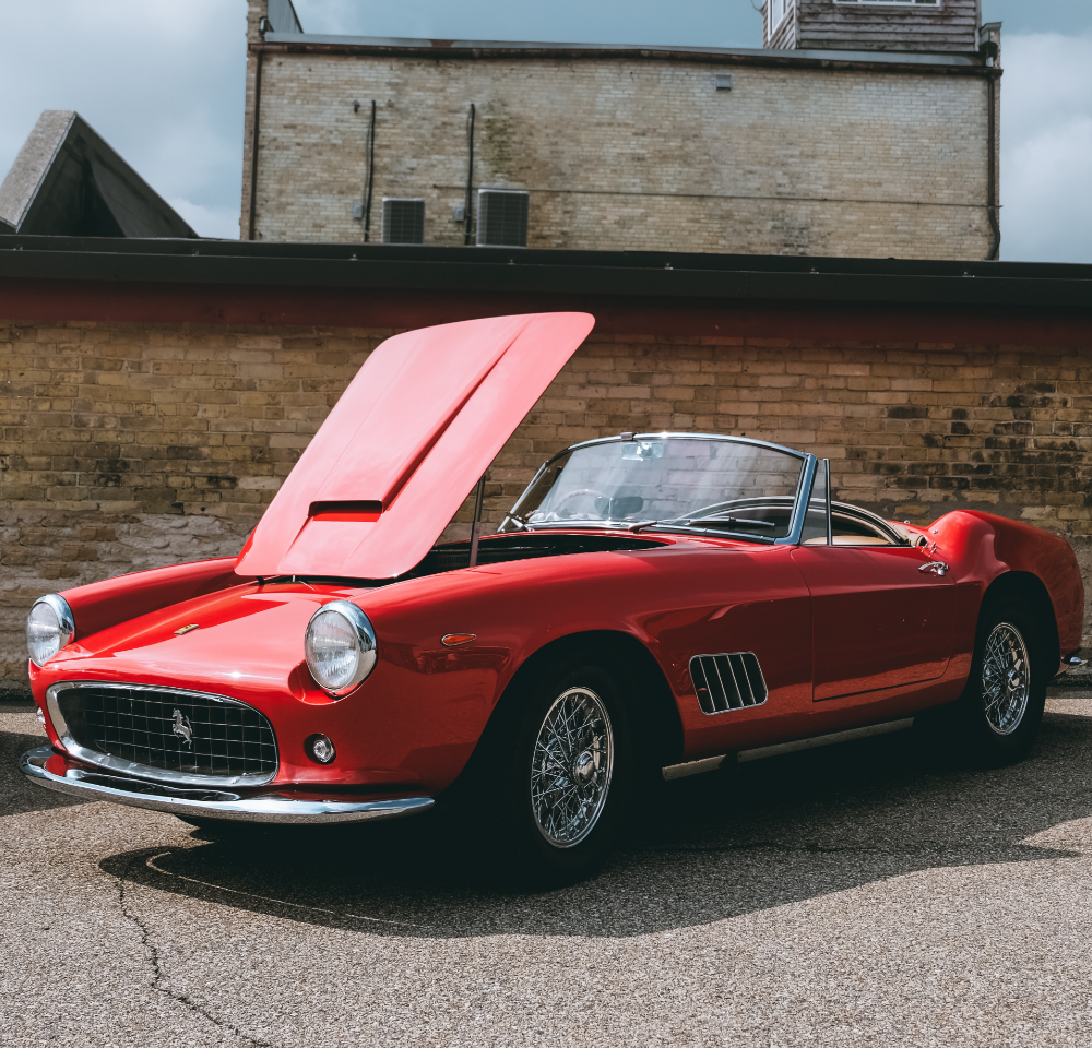 Red classic car with roof down and bonnet open