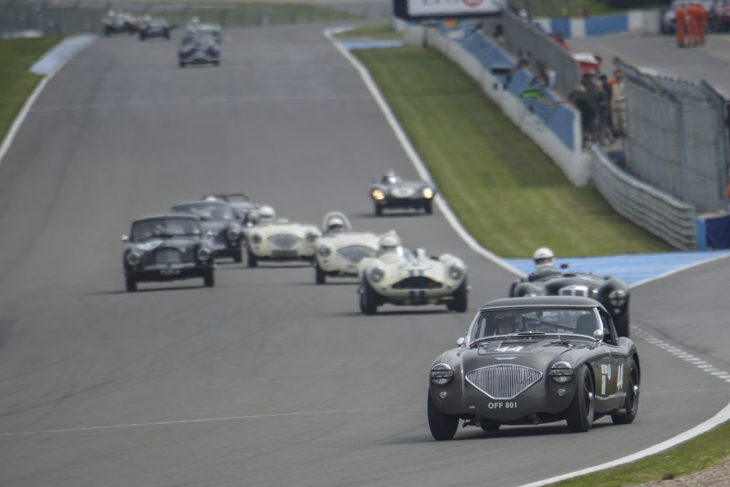 The Healey enters a bend ahead of assorted historic racers.