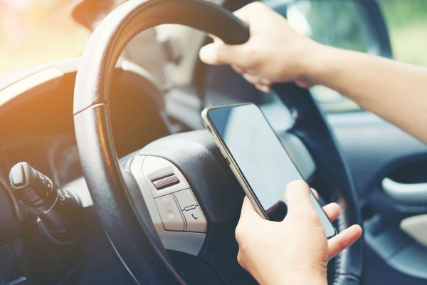 Person using their mobile phone while driving