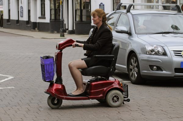 Woman crossing the road on her mobility scooter