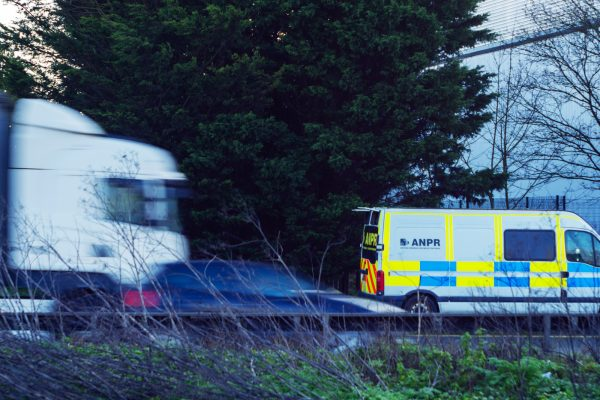 ANPR camera van on motorway with traffic passing in foreground in England UK