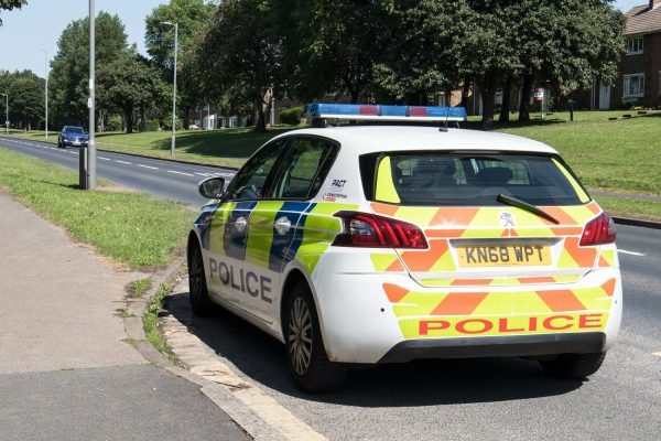 Police car parked at the side of a street road