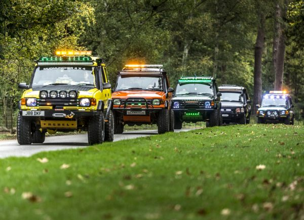 Different coloured Land Rovers in a rally driving down the road