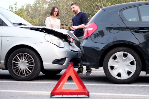 Two people exchanging insurance information after an accident