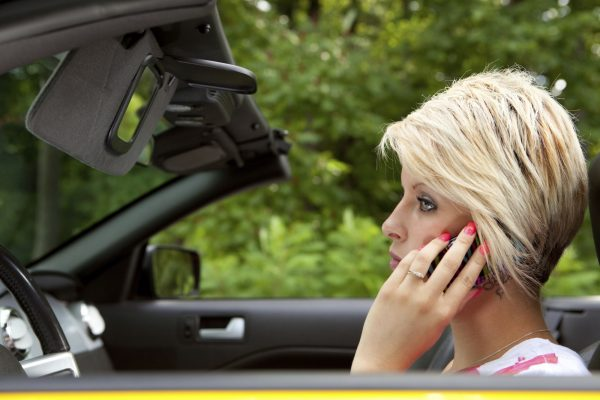 Woman driving carelessly by talking on the phone