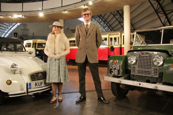 Vicki Butler-Henderson and Alex Riley in front of two cars