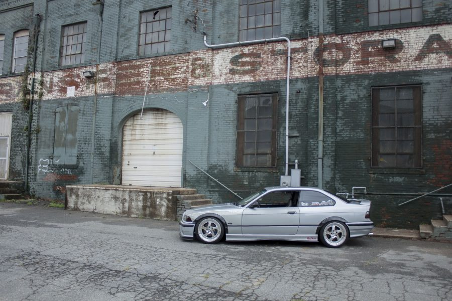 A modified BMW parked in front of a wall